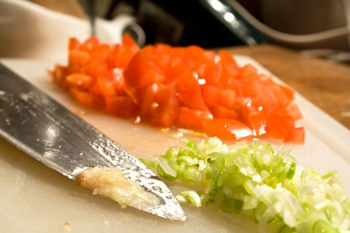 San marzano tomater og forårsløg finthakkede. Et halvt lille fed hvidløg knust med salt på knivsbladet
