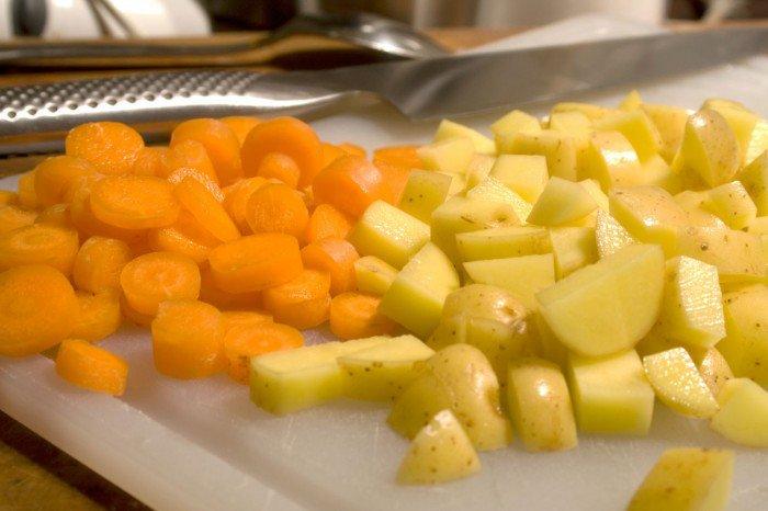 Gulerødder og kartofler hakkes i små stykker