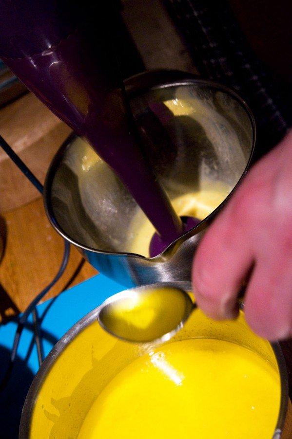 Lidt smør hældes ned til æggeblommerne mens der piskes/blendes