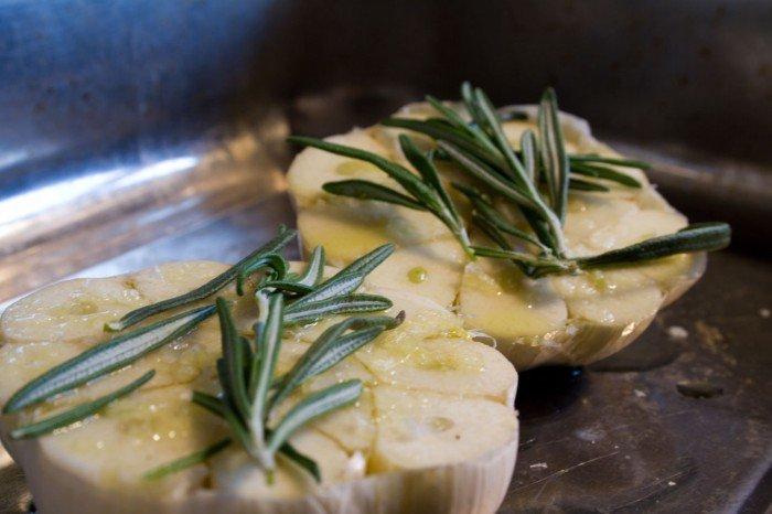 Halveret helt hvidløg, med salt, rosmarin og olivenolie