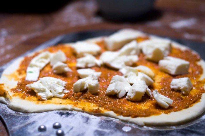 Basilikum mozzarella ligges på pizzaen