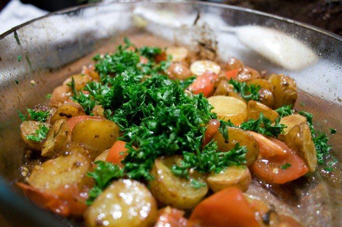 Den hakkede persille blandes i med de røde kartofler og tomaterne