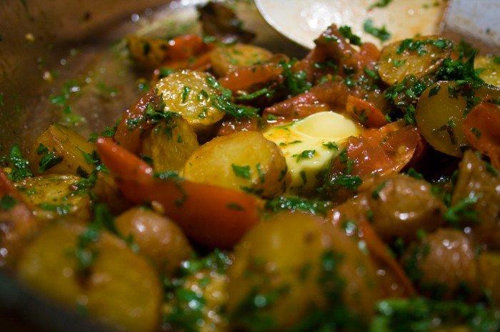 Smørret tilsættes de røde kartofler, tomater og persille