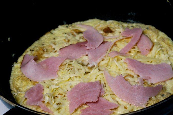 Omeletten blev vendt igen. Først lidt salt jævnt over det hele og så dækkes jævnt med reven ost og skinke