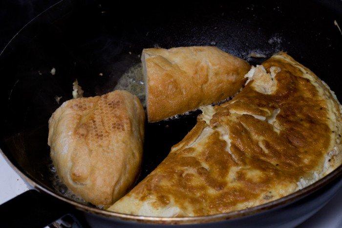 Omeletten foldet halvt sammen, mens to skiver flutes lige steges sprøde