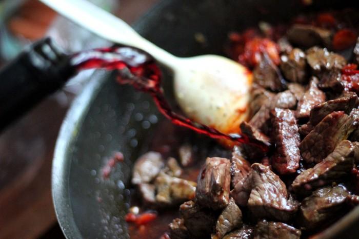 Tilsæt lidt under en halv flaske rødvin og lige så meget oksefond (eller vand med boullion i stedet)
