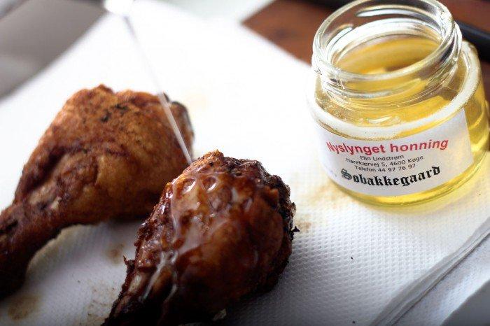 Dryp flydende honning over de stegte kyllinge lår
