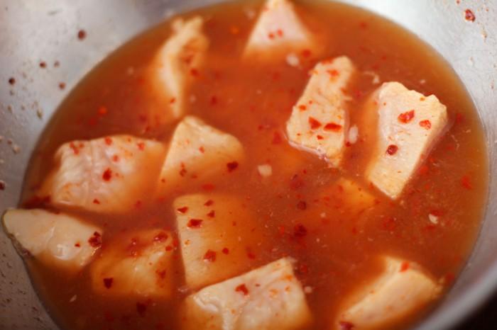Kyllingebrystet skæres i mindre stykkerog marineres i æblecider eddike, citronsaft og knust tørret chili