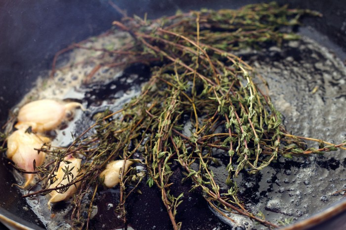 Timian og hvidløg steges med i smør inden kødet tilsættes