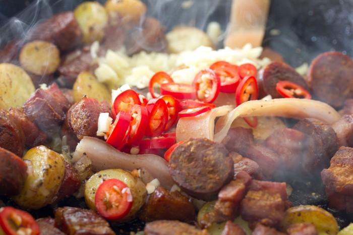 Chili og hvidløg skal på panden. Jeg lagde også bacon skindet på for smagens skyld