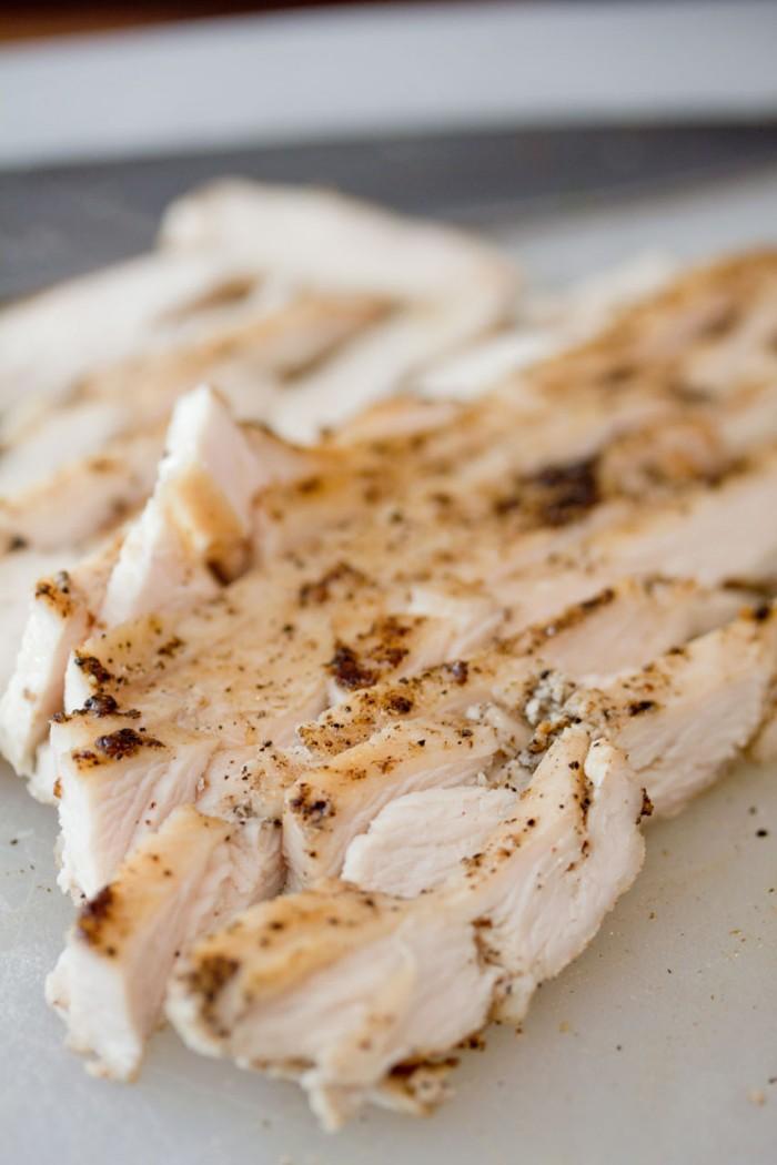 Skær det stegte kyllingebryst ud i tynde skiver