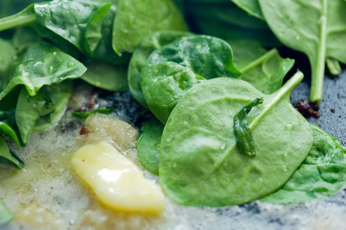 Hæld den vaskede spinat på den varme pande med smør og hvidløg mosen