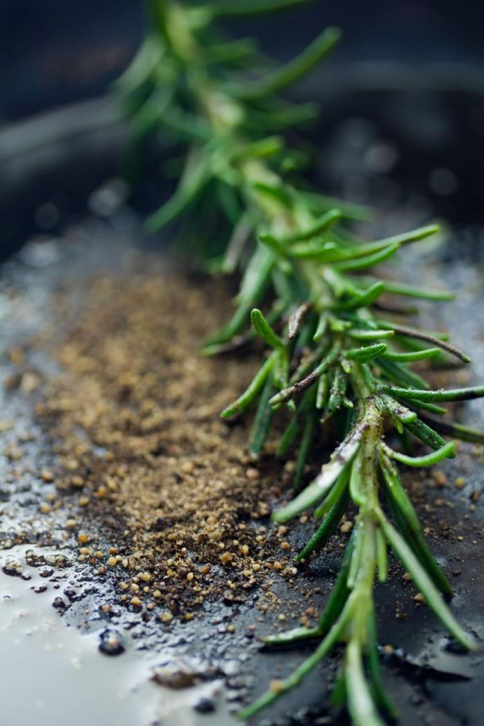 Lidt olie på panden sammen med frisk knust peber og en gren rosmarin