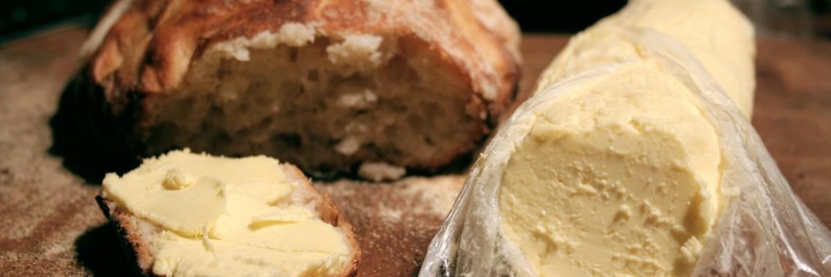 Den første bid brød med hjemmelavet smør, parat til at blive nydt